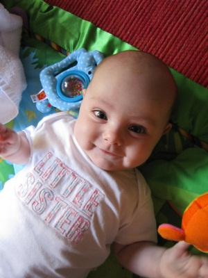 Evie Lattimore, 4 months old & smiling on play mat