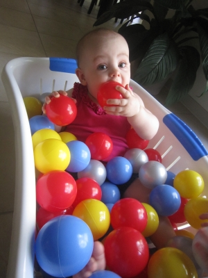 Evie sitting in a clothes basket full multi-coloured plastic balls