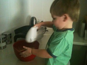 Hugo using the electric beater to mix pikelet mixture