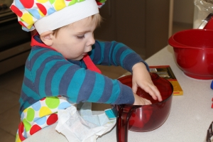 Hugo mixing cooking ingredients by hand wearing a chefs hat & apron