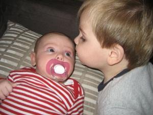 Hugo Lattimore kissing 2 month old Evie Lattimore on the forehead