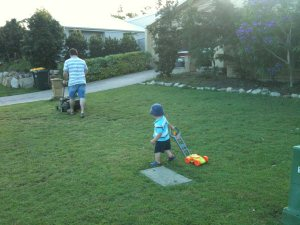 Hugo helping mow the lawn with toy plastic mower